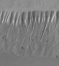 Evidence from Mars Global Surveyor (MGS) of relatively recent water flow down a valley side from underground aquifers.